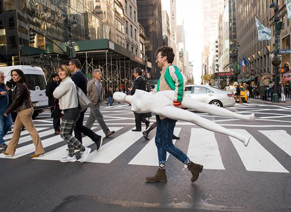 A student holding a mannequin crossing a city street.
