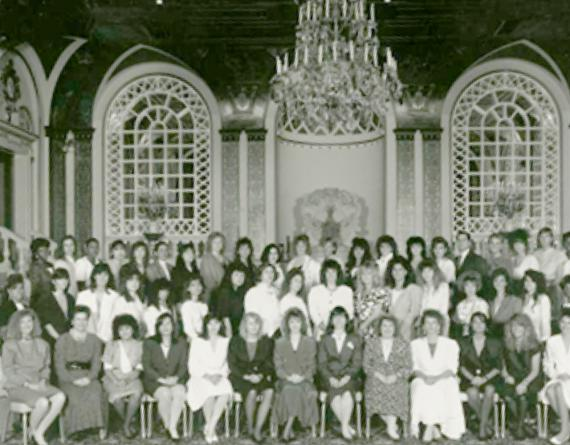 group of women in 1980s dresses in a ballroom