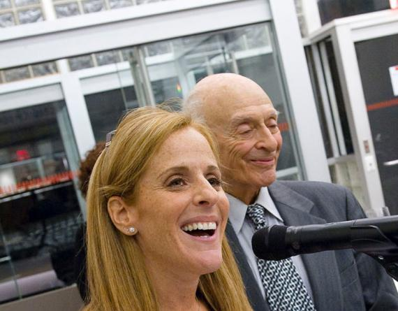 smiling man and woman at a microphone