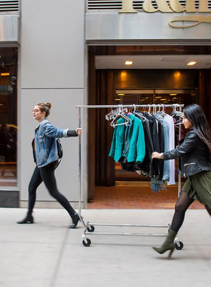 Two designers walking with a rack of clothing on the sidewalk.